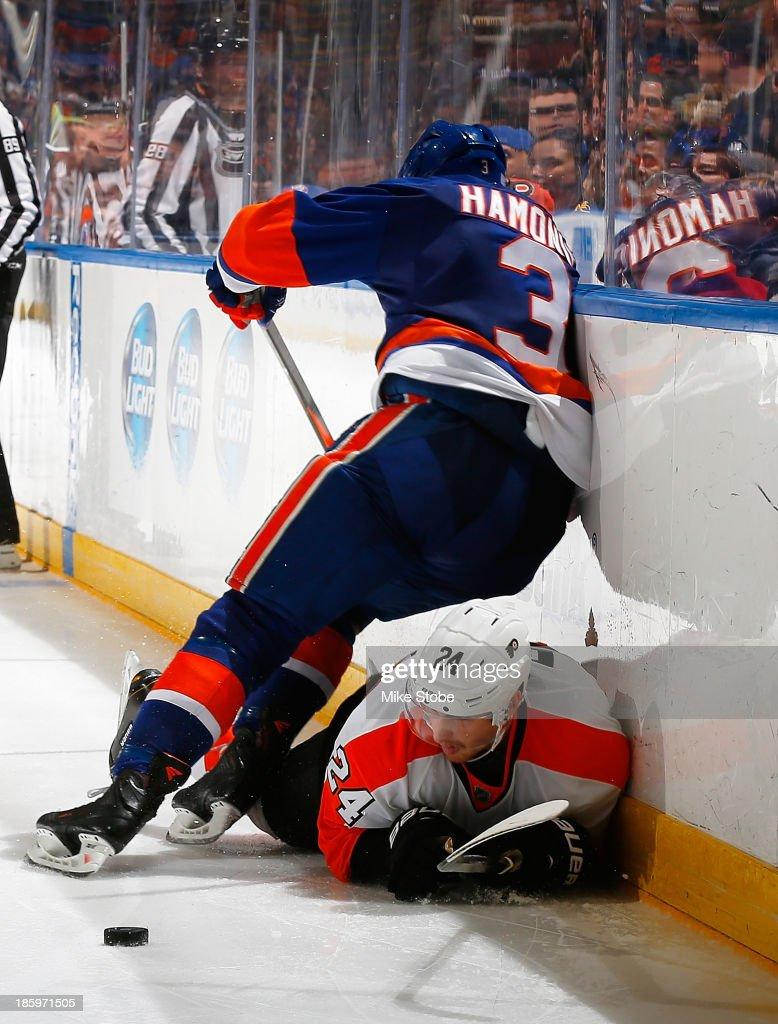 Matt Read of the Philadelphia Flyers falls to the ice battling for the puck with Travis Hamonic of the New York Islanders at Nassau Veterans Memorial...