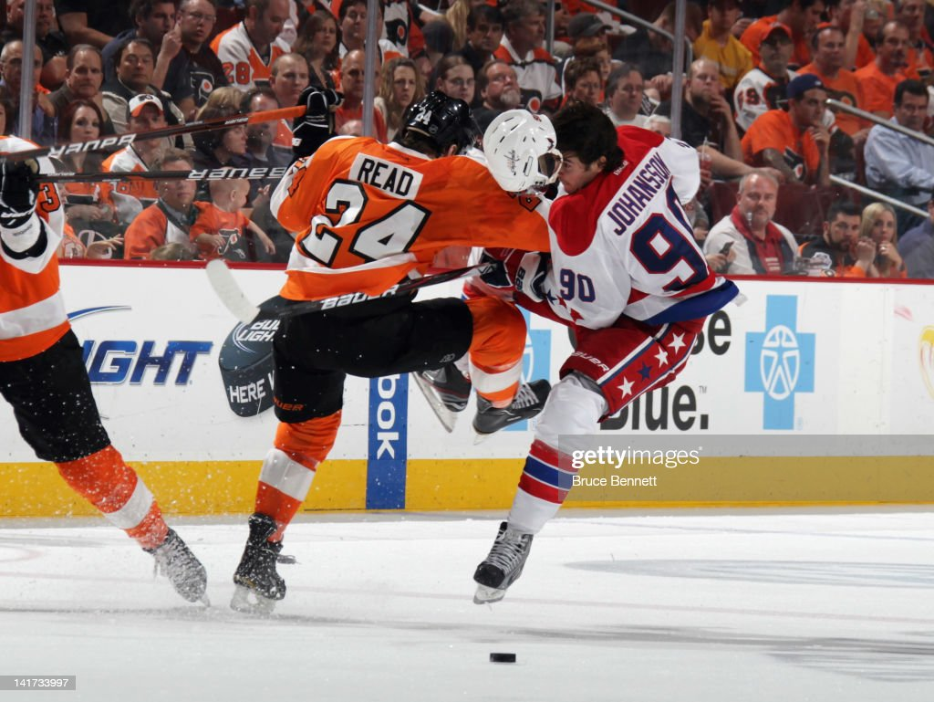 Matt Read of the Philadelphia Flyers hits Marcus Johansson of the Washington Capitals during the third period at the Wells Fargo Center on March 22...