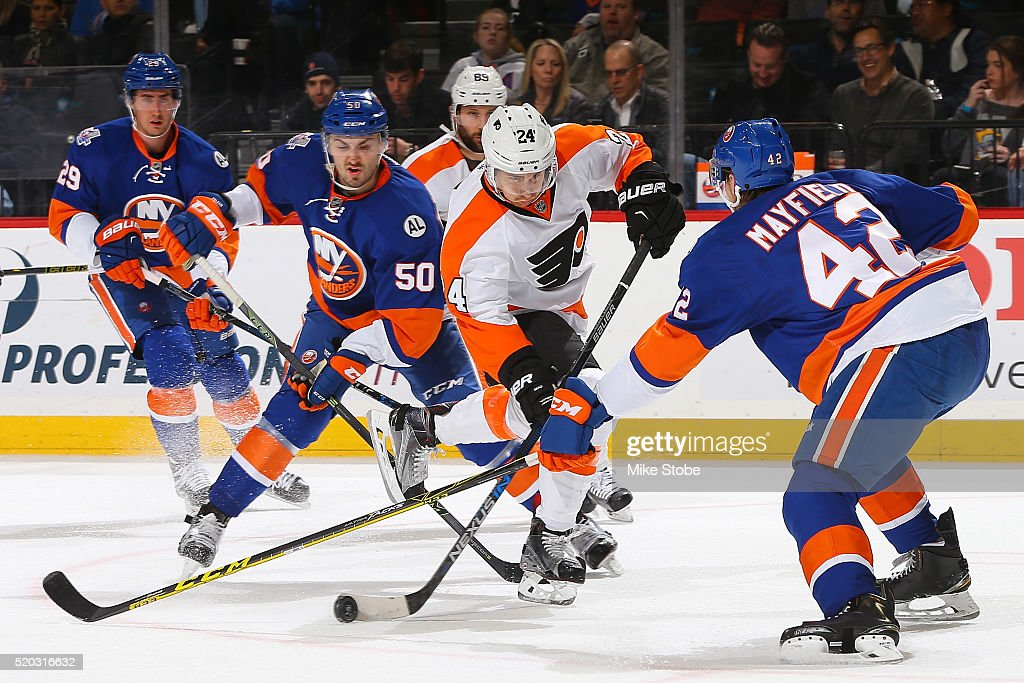 Matt Read of the Philadelphia Flyers plays the puck against Adam Pelech of the New York Islanders at the Barclays Center on April 10 2016 in Brooklyn...