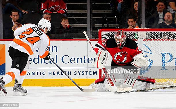 Matt Read of the Philadelphia Flyers scoes the game winning goal in overtime as Cory Schneider of the New Jersey Devils defends on December 4 2015 at...