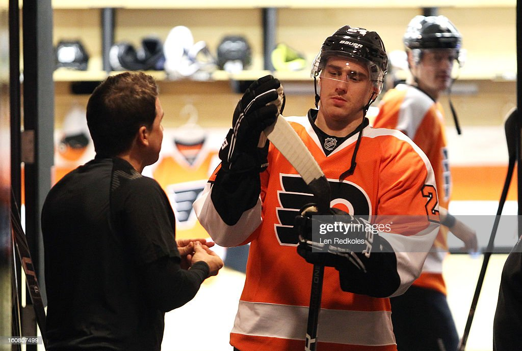 Matt Read #24 of the Philadelphia Flyers talks with equipment manager Derek Settlemyre as he prepares to enter the ice surface for warm-ups prior to his game against the Carolina Hurricanes on February 2, 2013 at the Wells Fargo Center in Philadelphia, Pennsylvania.