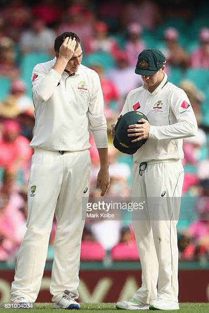 Matt Renshaw watches on as Steve Smith of Australia adjusts his helmet after Renshaw was hit on the helmet while fielding during day three of the...