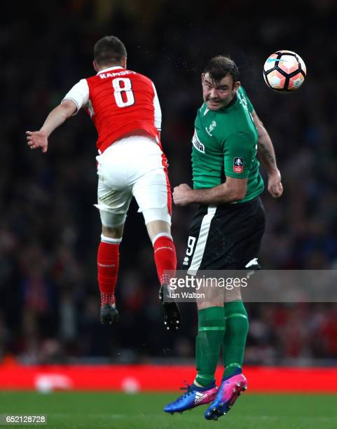 Matt Rhead of Lincoln City and Aaron Ramsey of Arsenal jump for the ball during The Emirates FA Cup QuarterFinal match between Arsenal and Lincoln...