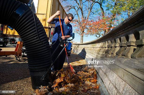 Matt Riley from the Architect of the Capitol office rakes up leaves on the west front of the Capitol