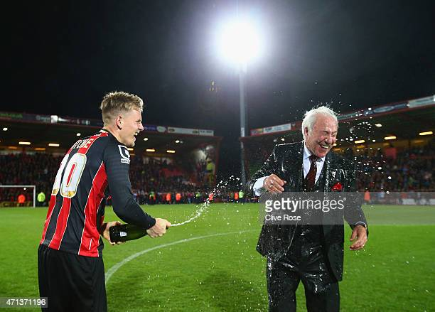 Matt Ritchie of Bournemouth sprays Bournemouth chairman Jeff Mostyn with champagne as they celebrate victory on the pitch after the Sky Bet...