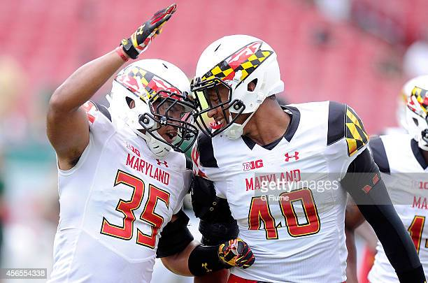 Matt Robinson and Alex Twine of the Maryland Terrapins celebrate a defensive play against the South Florida Bulls at Raymond James Stadium on...