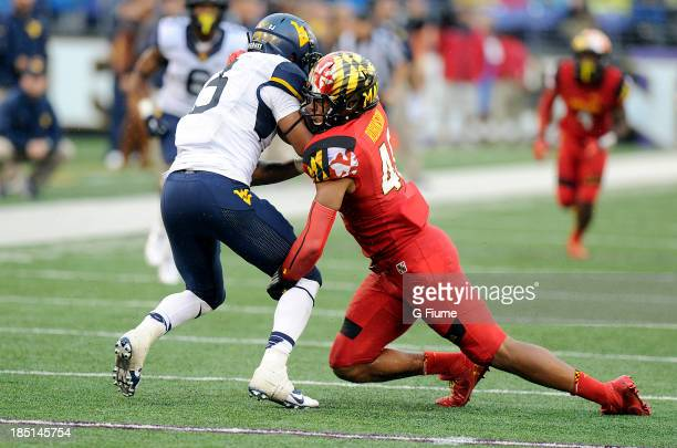 Matt Robinson of the Maryland Terrapins tackles Charles Sims of the West Virginia Mountaineers at MT Bank Stadium on September 212013 in Baltimore...