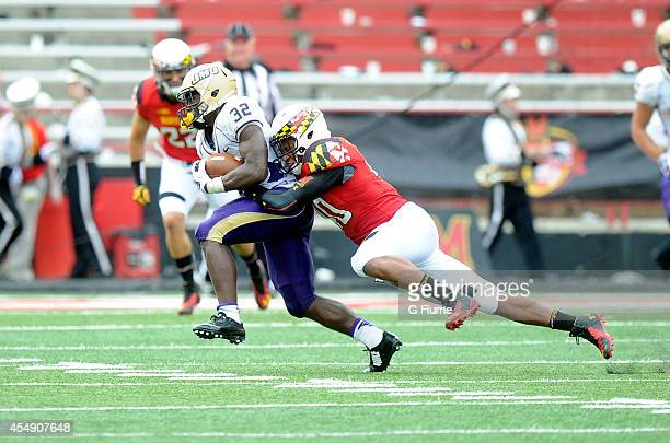 Matt Robinson of the Maryland Terrapins tackles Khalid Abdullah of the James Madison Dukes at Byrd Stadium on August 30 2014 in College Park Maryland