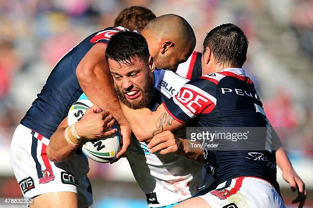 Matt Robinson of the Titans is tackled by the Roosters defence during the round 16 NRL match between the Sydney Roosters and the Gold Coast Titans at...