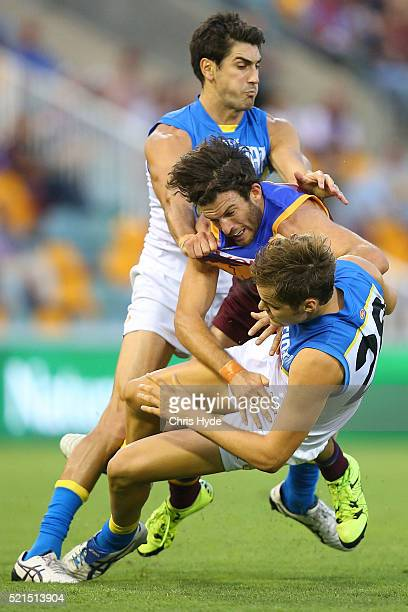 Matt Rosa and Kade Kolodjashnij of the Suns collide with Rohan Bewick of the Suns during the round four AFL match between the Brisbane Lions and the...