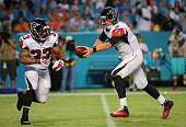 Matt Ryan hands off to Travis Howard of the Atlanta Falcons the ball during a preseason game against the Miami Dolphins at Sun Life Stadium on August...