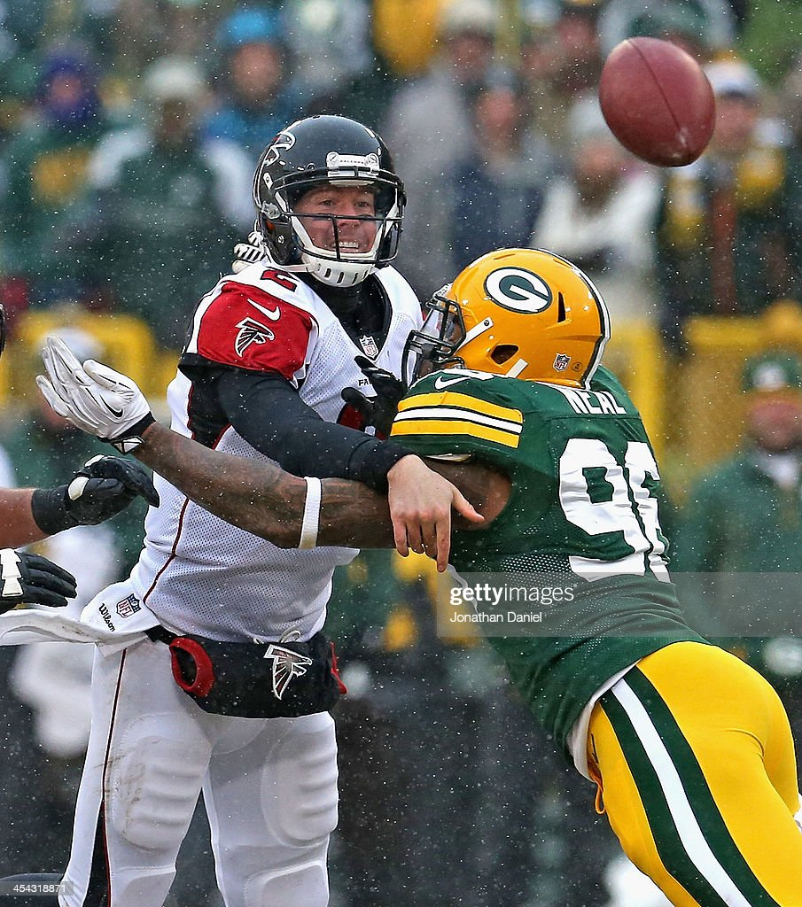 Matt Ryan #2 of the Atlanta Falcons is hit while passing by Mike Neal #96 of the Green Bay Packers at Lambeau Field on December 8, 2013 in Green Bay, Wisconsin. The Packers defeated the Falcons 22-21.