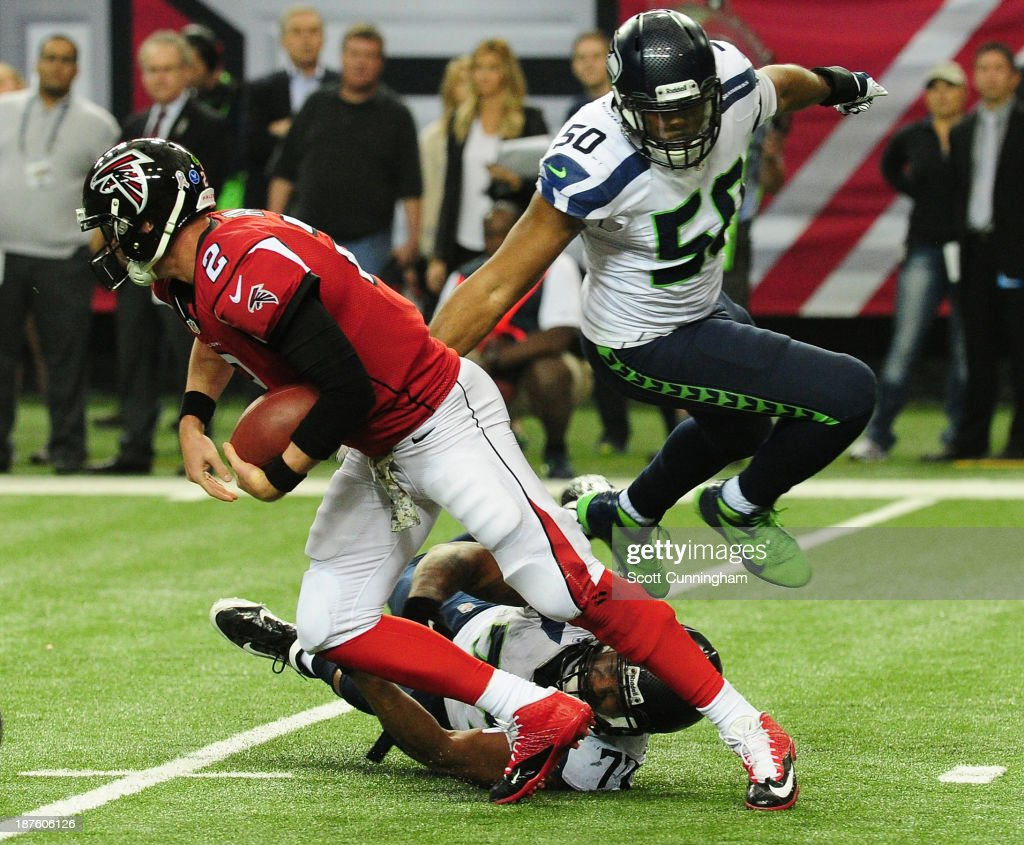 Matt Ryan #2 of the Atlanta Falcons is sacked by K. J. Wright #50 and <a gi-track='captionPersonalityLinkClicked' href=/galleries/search?phrase=Michael+Bennett+-+American+Football+Defensive+End+-+Born+1985&family=editorial&specificpeople=11360119 ng-click='$event.stopPropagation()'>Michael Bennett</a> #72 of the Seattle Seahawks at the Georgia Dome on November 10, 2013 in Atlanta, Georgia.