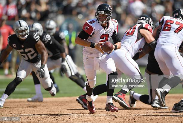 Matt Ryan of the Atlanta Falcons turns to hand the ball off to a running back against the Oakland Raiders in the first haft of their NFL game at...