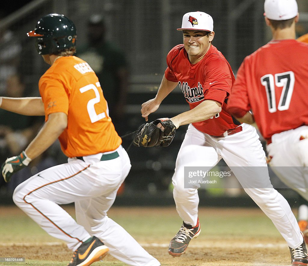 Matt Schmitt #37 of the Illinois State Redbirds tags out Brad Fieger #27 of the Miami Hurricanes in a rundown between third base and home pate on March 13, 2013 at Alex Rodriguez Park at Mark Light Field in Coral Gables, Florida. The Hurricanes defeated the Redbirds 9-2.