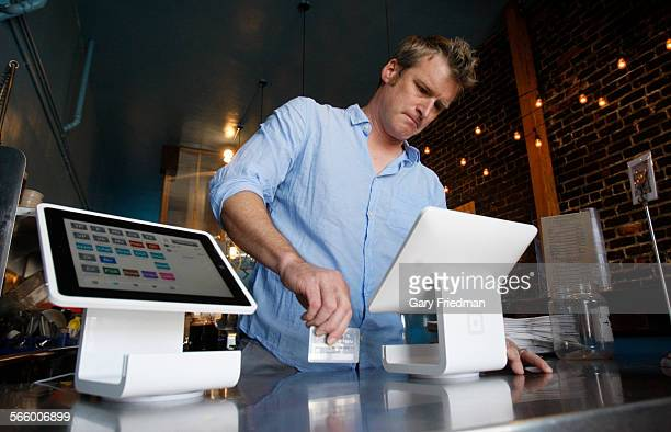 Matt Schodorf owner of Schodorf's Luncheonette swipes a credit card on the Square Stand at his restaurant of which he owns in the Highland Park area...