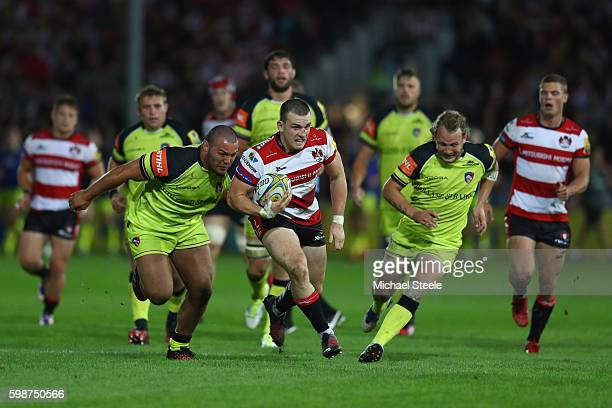 Matt Scott of Gloucester bursts clear of Ellis Genge and Sam Harrison of Leicester during the Aviva Premiership match between Gloucester and...