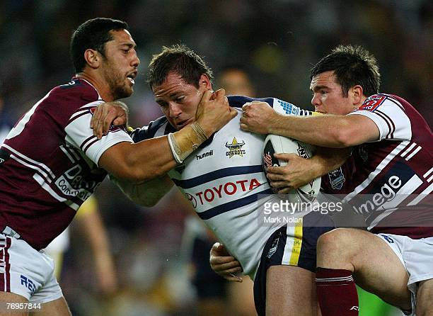 Matt Scott of the Cowboys is tackled by Brent Kite and Jamie Lyon of the Eagles during the first preliminary final NRL match between the...