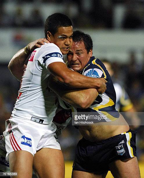 Matt Scott of the Cowboys is tackled by Chase Stanley of the Dragons during the round 23 NRL match between the North Queensland Cowboys and the St...