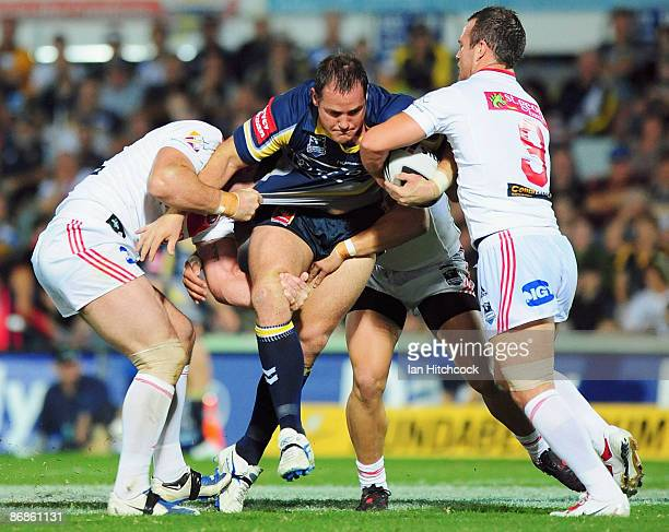 Matt Scott of the Cowboys is wrapped up by the Dragons defence during the round nine NRL match between the North Queensland Cowboys and the St George...