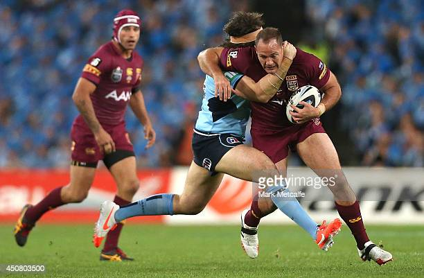Matt Scott of the Maroons is tackled by Aaron Woods of the Blues during game two of the State of Origin series between the New South Wales Blues and...
