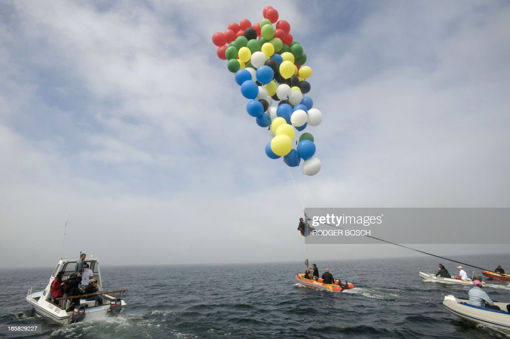 Matt Silver-Vallance flies above Table Bay, with some of his support crew in boats from Nelson Mandela's apartheid island prison using helium-filled giant party balloons, on April 6, 2013 in Cape Town. The six-kilometre (3.7-mile) crossing, to raise funds for a children's hospital named after the country's former president, was the first stunt of its kind from the historical site. Silver-Vallance, 37, took around an hour to float across the Atlantic Ocean from Robben Island while harnessed to a mass of multi-coloured balloons in grey, drizzly conditions with low visibility. BOSCH