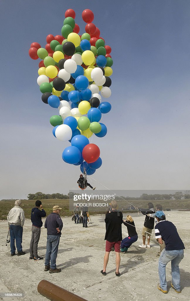 Matt Silver-Vallance (C) gets ready prior to flew across the sea from Nelson Mandela's apartheid island prison using helium-filled giant party balloons, on April 6, 2013 in Cape Town. The six-kilometre (3.7-mile) crossing, to raise funds for a children's hospital named after the country's former president, was the first stunt of its kind from the historical site. Silver-Vallance, 37, took around an hour to float across the Atlantic Ocean from Robben Island while harnessed to a mass of multi-coloured balloons in grey, drizzly conditions with low visibility. BOSCH