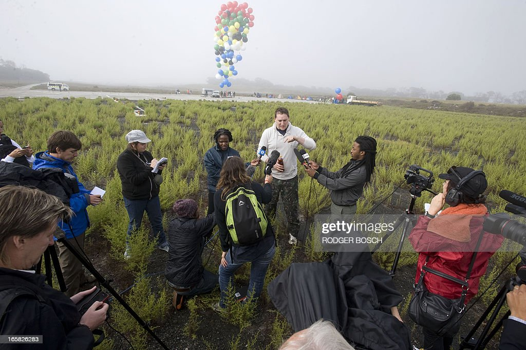 Matt Silver-Vallance talks to the press prior to flew across the sea from Nelson Mandela's apartheid island prison using helium-filled giant party balloons, on April 6, 2013 in Cape Town. The six-kilometre (3.7-mile) crossing, to raise funds for a children's hospital named after the country's former president, was the first stunt of its kind from the historical site. Silver-Vallance, 37, took around an hour to float across the Atlantic Ocean from Robben Island while harnessed to a mass of multi-coloured balloons in grey, drizzly conditions with low visibility. BOSCH