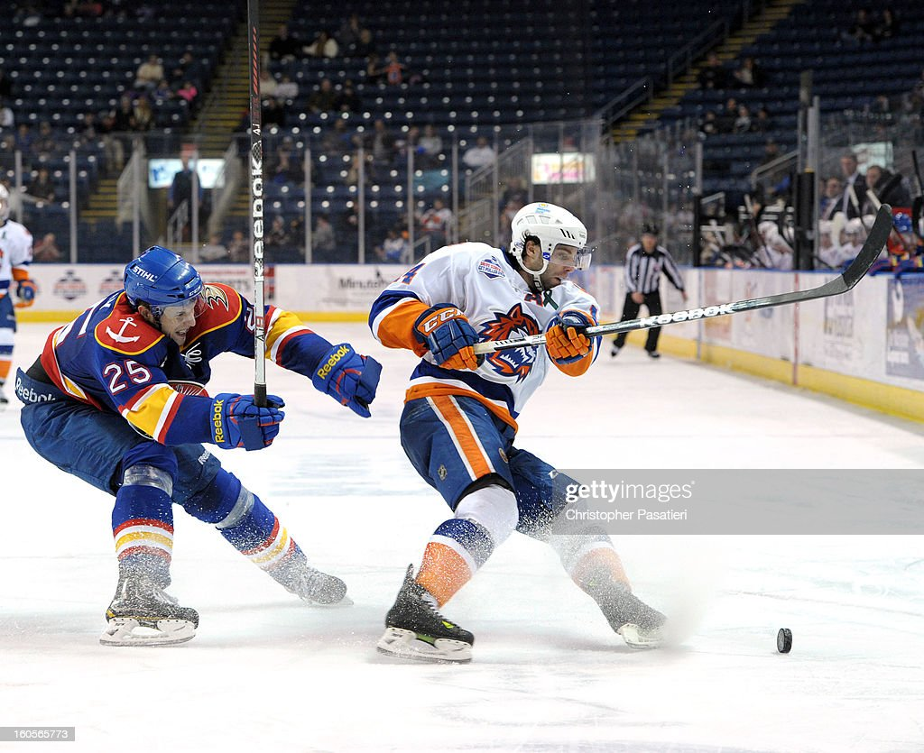 Matt Smaby #25 of the Norfolk Admirals and Matt Watkins #14 of the Bridgeport Sound Tigers skate after the puck during an American Hockey League game on February 2, 2013 at the Webster Bank Arena at Harbor Yard in Bridgeport, Connecticut.