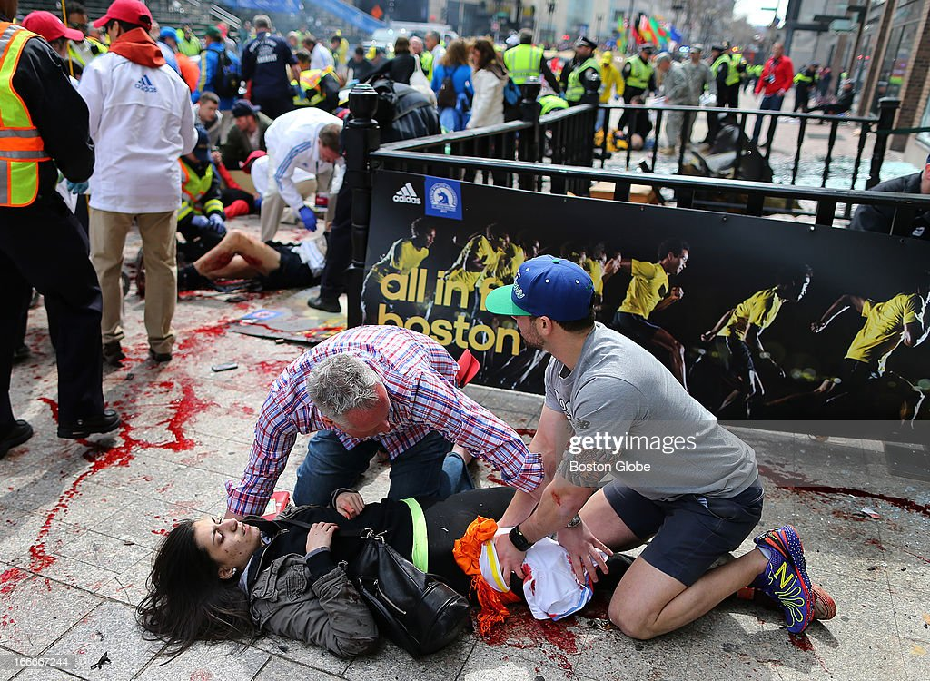 Matt Smith (left) of Boston and Zach Mione of Portland, Ore., helped Sydney Corcoran of Lowell on the Boylston Street sidewalk at the scene of the first explosion near the finish line of the 117th Boston Marathon. They applied pressure and tried to stop the bleeding of her injured leg.