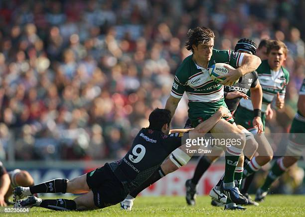 Matt Smith of Leicester evades a tackle from Rhodri Wells of Ospreys during the Heineken Cup match between Leicester Tigers and Ospreys at Welford...
