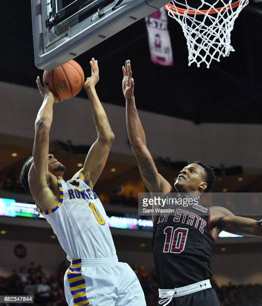 Matt Smith of the Cal State Bakersfield Roadrunners shoots against Jemerrio Jones of the New Mexico State Aggies during the championship game of the...