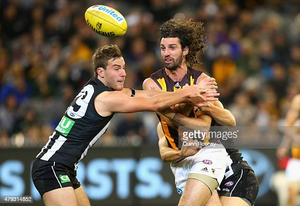 Matt Spangher of the Hawks handballs whilst being tackled by Tim Broomhead of the Magpies during the round 14 AFL match between the Collingwood...