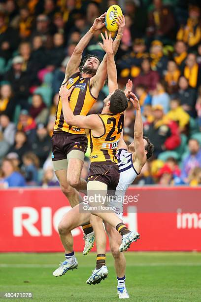 Matt Spangher of the Hawks marks over the top of Ben Stratton of the Hawks and Hayden Ballantyne of the Dockers during the round 15 AFL match between...