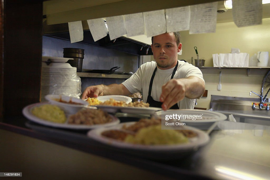 Matt Spoon prepares food for customers at Bill Spoon's Barbecue on July 12, 2012 in Charlotte, North Carolina. The nearly fifty-year-old restaurant, founded by Matt's grandfather, is known for its Eastern North Carolina Style BBQ served with homemade vinegar based BBQ sauce, mustard based coleslaw, and made-from-scratch hushpuppies. The restaurant was recently recognized as one of the ten best BBQ restaurants in the United States. Businesses in Charlotte are anticipating a boost in sales when an estimated 35,000 visitors arrive in the city for the 2012 Democratic National Convention (DNC) September 3-6.