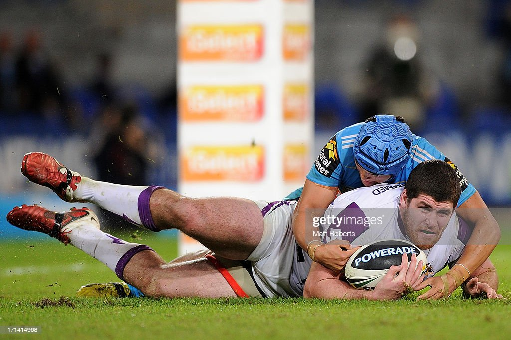 Matt Srama of the Titans tackles Mitchell Garbutt of the Storm during the round 15 NRL match between the Gold Coast Titans and the Melbourne Storm at Skilled Park on June 24, 2013 on the Gold Coast, Australia.