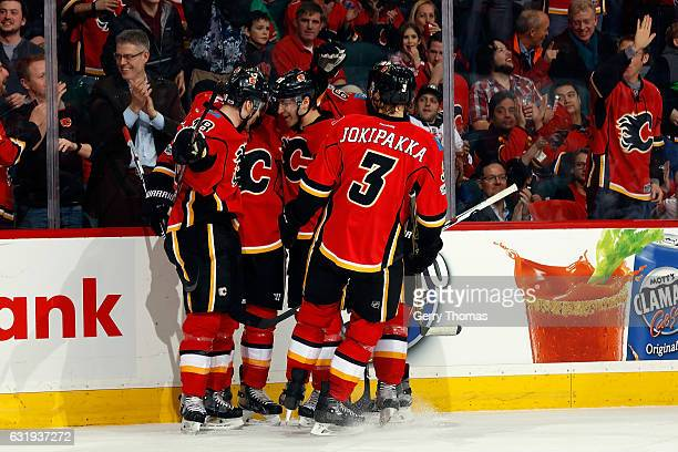 Matt Stajan Jyrki Jokipakka and teammates of the Calgary Flames celebrate a goal agains the Florida Panthers during an NHL game on January 17 2017 at...