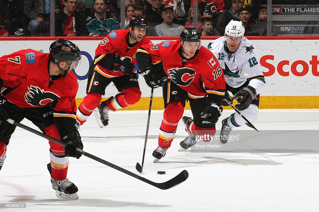 Matt Stajan #18, Mark Giordano #5 and T.J. Brodie #7 of the Calgary Flames skate against Patrick Marleau #12 of the San Jose Sharks at Scotiabank Saddledome on March 24, 2014 in Calgary, Alberta, Canada.