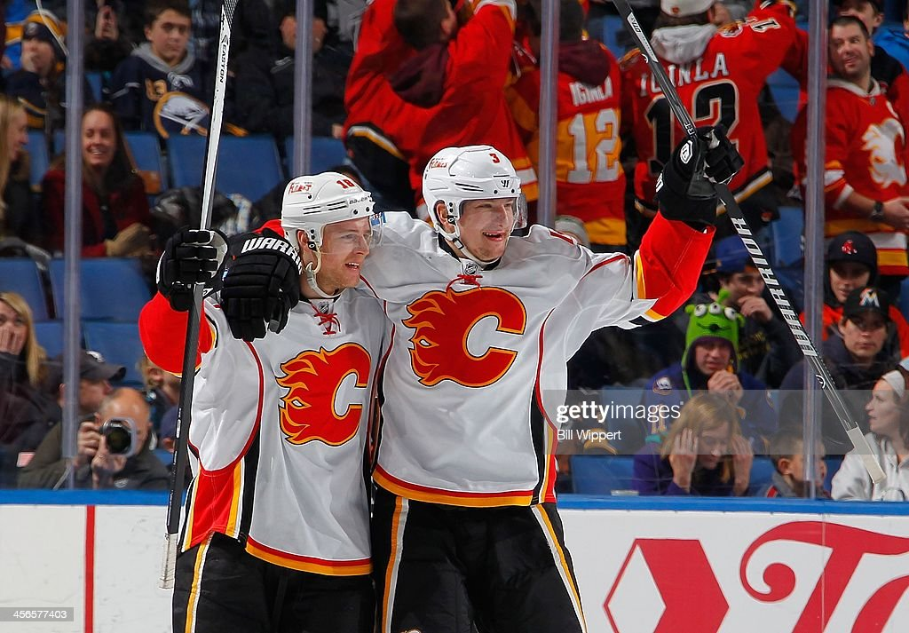 Matt Stajan #18 of the Calgary Flames celebrates his game winning overtime goal with teammate Ladislav Smid #3 against the Buffalo Sabres on December 14, 2013 at the First Niagara Center in Buffalo, New York. Calgary won, 2-1.