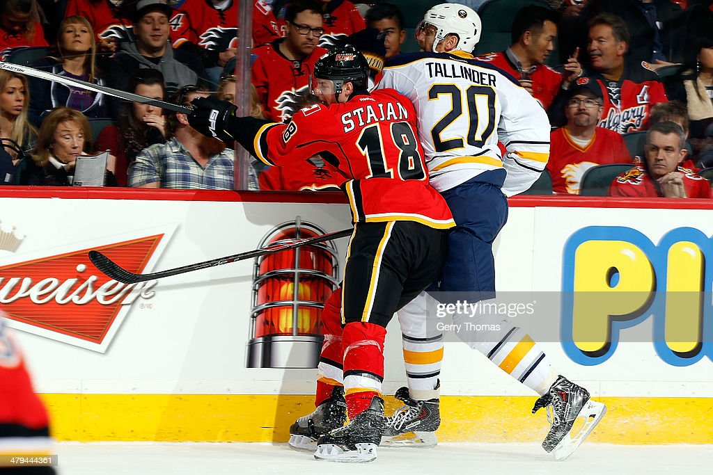 Matt Stajan #18 of the Calgary Flames checks <a gi-track='captionPersonalityLinkClicked' href=/galleries/search?phrase=Henrik+Tallinder&family=editorial&specificpeople=204661 ng-click='$event.stopPropagation()'>Henrik Tallinder</a> #20 of the Buffalo Sabres at Scotiabank Saddledome on March 18, 2014 in Calgary, Alberta, Canada.