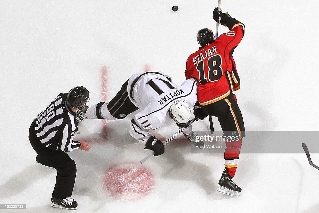 Matt Stajan #18 of the Calgary Flames faces off against <a gi-track='captionPersonalityLinkClicked' href=/galleries/search?phrase=Anze+Kopitar&family=editorial&specificpeople=634911 ng-click='$event.stopPropagation()'>Anze Kopitar</a> #11 of the Los Angeles Kings on February 20, 2013 at the Scotiabank Saddledome in Calgary, Alberta, Canada.