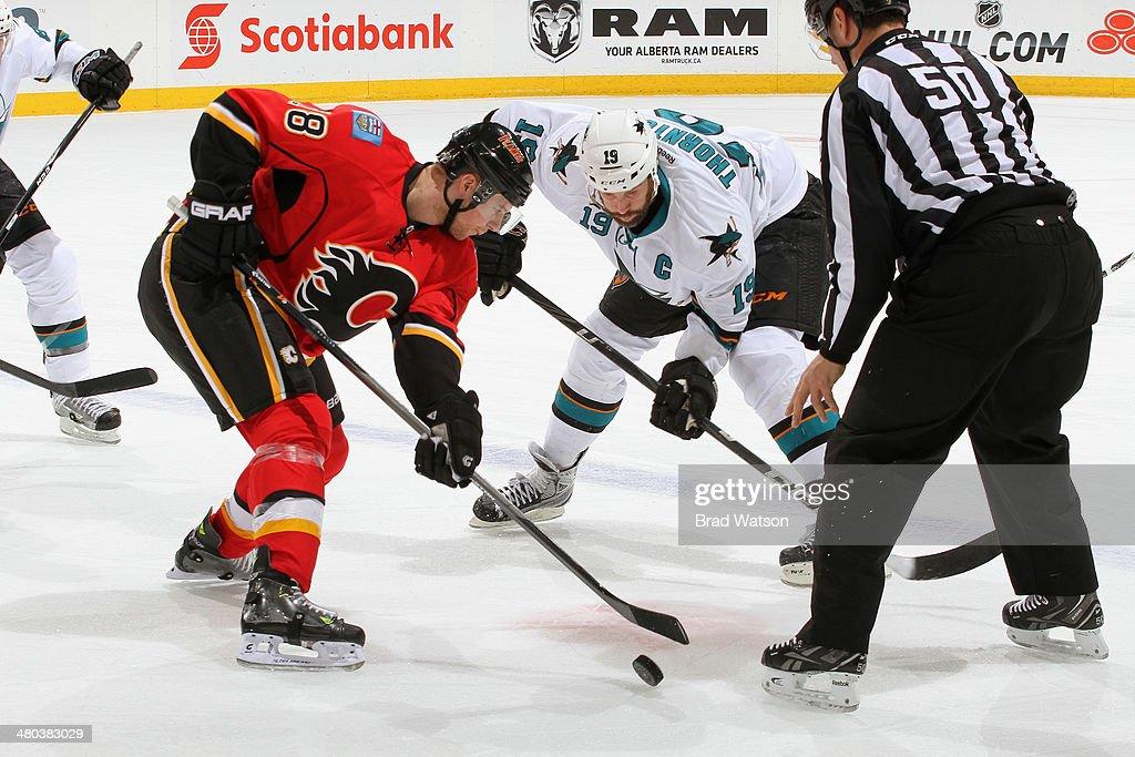 Matt Stajan #18 of the Calgary Flames faces off against Joe Thornton #19 of the San Jose Sharks at Scotiabank Saddledome on March 24, 2014 in Calgary, Alberta, Canada.