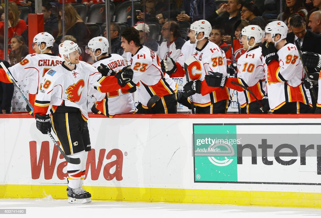 Matt Stajan #18 of the Calgary Flames is congratulated by his teammates after scoring a third-period goal to tie the game against the New Jersey Devils at Prudential Center on February 3, 2017 in Newark, New Jersey.