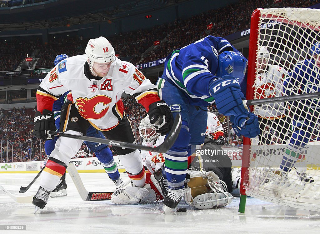 Matt Stajan #18 of the Calgary Flames pushes <a gi-track='captionPersonalityLinkClicked' href=/galleries/search?phrase=Brad+Richardson&family=editorial&specificpeople=638058 ng-click='$event.stopPropagation()'>Brad Richardson</a> #15 of the Vancouver Canucks at the Calgary goal during their NHL game at Rogers Arena April 13, 2014 in Vancouver, British Columbia, Canada. Vancouver won 5-1.