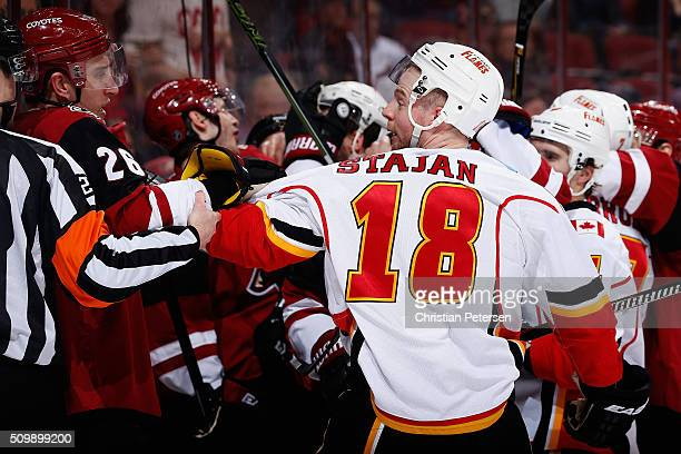 Matt Stajan of the Calgary Flames pushes Michael Stone of the Arizona Coyotes in a scrum after Stajan was checked into the boards during the third...