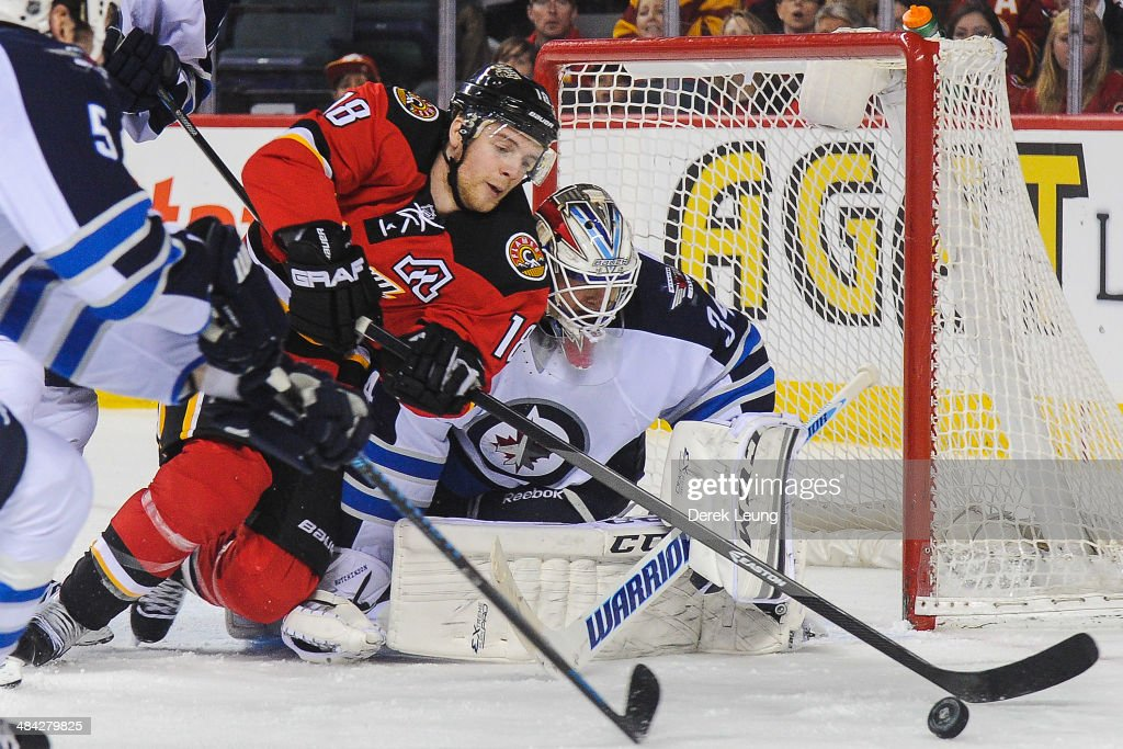 Matt Stajan #18 of the Calgary Flames reaches for the loose puck in front of Michael Hutchinson #34 of the Winnipeg Jets during an NHL game at Scotiabank Saddledome on April 11, 2014 in Calgary, Alberta, Canada. The Jets defeated the Flames 5-3.