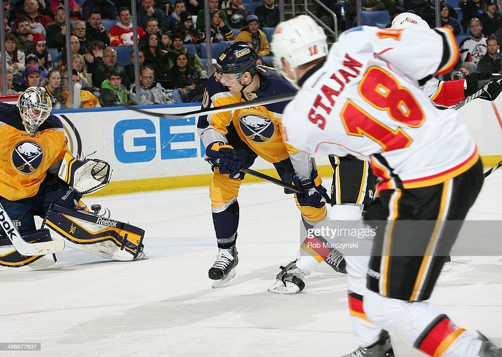 Matt Stajan #18 of the Calgary Flames scores the game winning overtime goal against Jhonas Enroth #1 of the Buffalo Sabres on December 14, 2013 at the First Niagara Center in Buffalo, New York. Calgary won, 2-1.