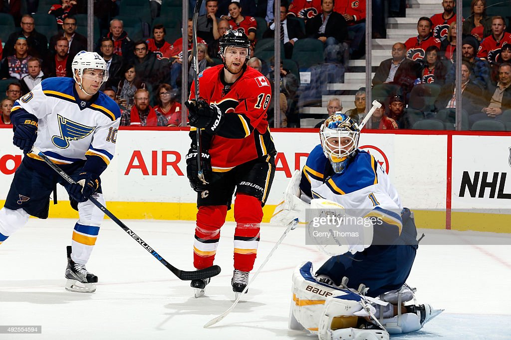 Matt Stajan #18 of the Calgary Flames skates against Scottie Upshall #10 and Brian Elliot #1 of the St. Louis Blues during an NHL game at Scotiabank Saddledome on October 13, 2015 in Calgary, Alberta, Canada.