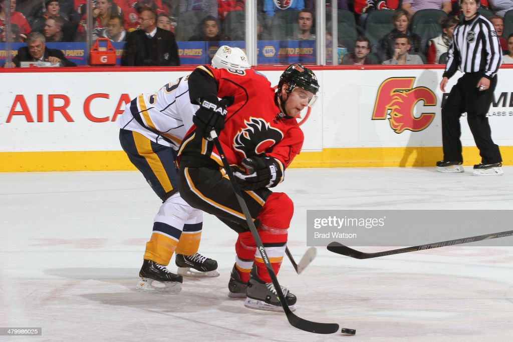 Matt Stajan #18 of the Calgary Flames skates the puck against <a gi-track='captionPersonalityLinkClicked' href=/galleries/search?phrase=Mike+Fisher+-+Ice+Hockey+Player&family=editorial&specificpeople=204732 ng-click='$event.stopPropagation()'>Mike Fisher</a> #12 of the Nashville Predators at Scotiabank Saddledome on March 21, 2014 in Calgary, Alberta, Canada.