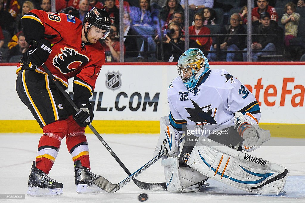 Matt Stajan #18 of the Calgary Flames takes a shot on Alex Stalock #32 of the San Jose Sharks during an NHL game at Scotiabank Saddledome on March 24, 2014 in Calgary, Alberta, Canada. The Flames defeated the Sharks 2-1 in shootout.